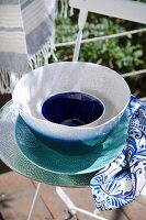 Bowls in shades of blue on garden chair