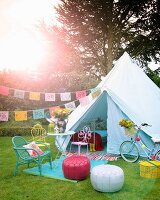 Party atmosphere in garden: seating area with colourful seats in front of tent decorated with bunting