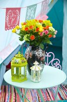 Painted lanterns and vase of colourful summer flowers on garden table