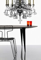 Artistic metal chandelier with stylised figures and symbols hanging over designer table and wire chair