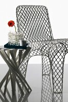 Wire mesh chair, side table with spiral twist of leg elements and gerbera daisy in coral-shaped vase