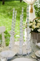White and grey striped candles in white candlesticks between place settings