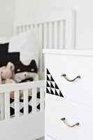 White chest of drawers with brass handles and geometric pattern