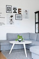 White, retro side table on black and white patterned rug in front of grey corner sofa