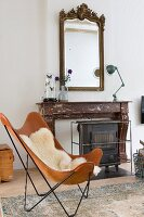 Leather Butterfly chair with sheepskin blanket in front of fireplace with marble surround, retro lamp and antique mirror