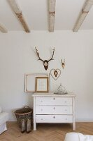 Antlers above white, vintage chest of drawers in bedroom with exposed ceiling beams