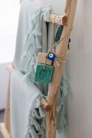 Fringed towels and bars of soap on cords hanging on wooden ladder