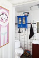 Poster hanging on door leading into toilet with blue-painted, wall-mounted cabinet