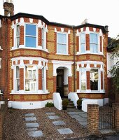 English terraced house with white elements in brick facade