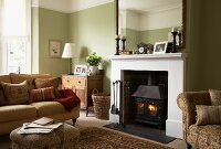 A cosy, traditional living room with a light green wall and a sofa in front of an open fireplace