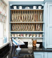 Pale blue country-house kitchen cabinet with integrated plate rack