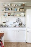 Simple, white kitchen counter with vintage crockery on wall-mounted shelves and retro-style fridge