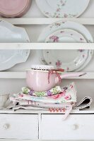 Pink saucepan and floral tea towels in front of vintage plates on plate rack