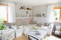 Comfortable living area with white-painted coffee table and bench in corner of vintage-style room painted pale grey