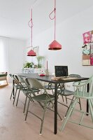 Black metal table, vintage folding chairs painted green and pendant lamps with pink lampshades in minimalist interior