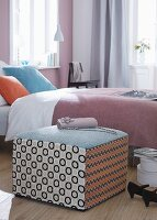 A patchwork pouffe as a bedside table or a seat next to a bed with a lilac bedspread