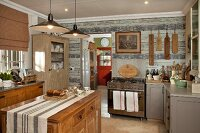 Rustic, country-house kitchen with free-standing, solid-wood island counter below pendant lamps with metal lampshades