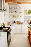 Pastel-coloured and white crockery on floating shelves above white, modern kitchen counter; untreated wood-beamed ceiling and gas cooker