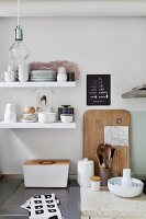 Crockery on white floating shelves above bread bin and kitchen utensils
