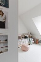 Pink pouffe next to bed in attic bedroom with white wooden floor