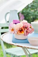 Arrangement of salmon-pink violas in china bowl on garden table
