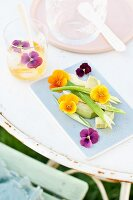 Sliced avocado arranged with spring onions and viola flowers