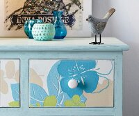 Blue chest of drawers decorated with floral wallpaper on front