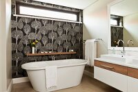 Free-standing bathtub against wall with transom window and black and white, tree-patterned wallpaper in designer bathroom