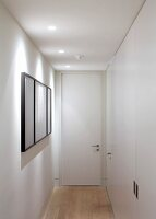 Private Apartment, London, United Kingdom. Architect: Hill Mitchell Berry, 2014. Narrow white hallway with recessed spotlights in suspended ceiling