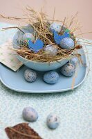 Dyed quail's eggs in straw Easter nest in pale blue bowl with matching plate
