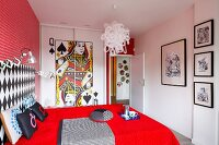 Bold, red bedroom with playing card motif on front of fitted wardrobes and gallery of black and white artworks