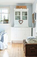 White, country-house-style dresser and old trunk on wooden floor in rustic interior