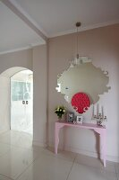 Pale pink console table below modern mirror and glass sliding doors in elegant hallway