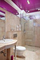 Elegant bathroom tiled in beige marble (Breccia Sarda) with purple ceiling panel