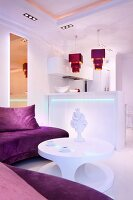 Atmospherically lit, white kitchen counter with purple pendant lamps in elegant, open-plan living area
