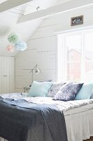 Scatter cushions and blankets on bed below window in wood-clad attic room decorated with pastel paper pompoms
