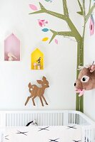 Cot in corner of room with mural: stylised tree with fairy lights, deer ornaments and display cases on wall