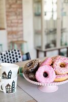 Iced donuts on cake stand and stacked coffee mugs