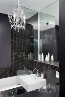 Small chandelier in designer bathroom with black mosaic tiles