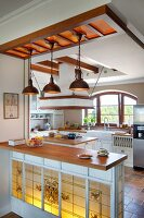 Wooden kitchen counter with backlit, traditional-style, stained-glass panel on front below rustic pendant lamps in open-plan, country-house kitchen