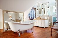 Free-standing bathtub on silver-gilt claw feet in front of framed mirror and twin washstand on wooden floor in spacious bathroom