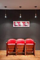 Red, retro cinema seats below Andy Warhol pop art picture on dark grey wall and designer pendant lamps