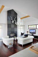 Elegant, white leather sofa set in front of fireplace integrated into wall covered in slate tiles