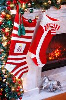 Knitted Christmas stockings hung on festively decorated mantelpiece