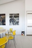 Yellow retro chairs around table and pictures on wall in modern interior with tiled floor