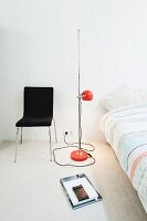Retro standard lamp with red, spherical lampshade between black chair and bed