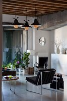 Living area with designer chairs, house plants and vintage pendant lamps in loft apartment