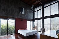 Loft-apartment bedroom with high ceiling and glass façade with louvre blinds