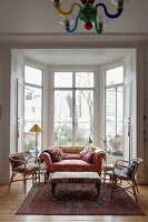 Wicker chairs and sofa around ottoman in window bay of living room with rustic ambiance