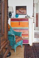 Wicker armchair painted turquoise in front chest of drawers with multi-coloured drawers